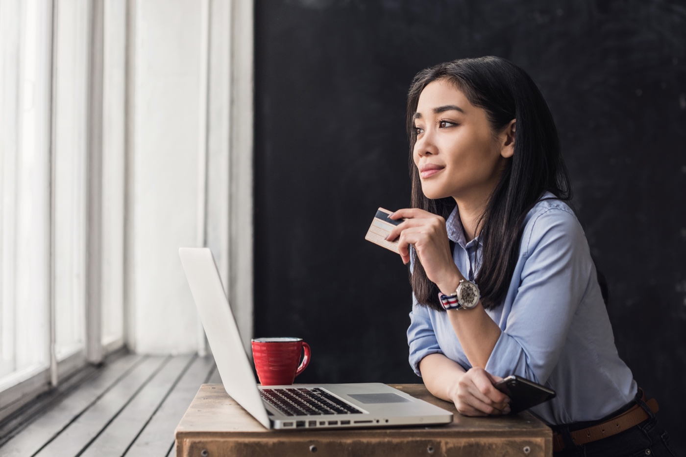 Woman at laptop with flex spending card in hand