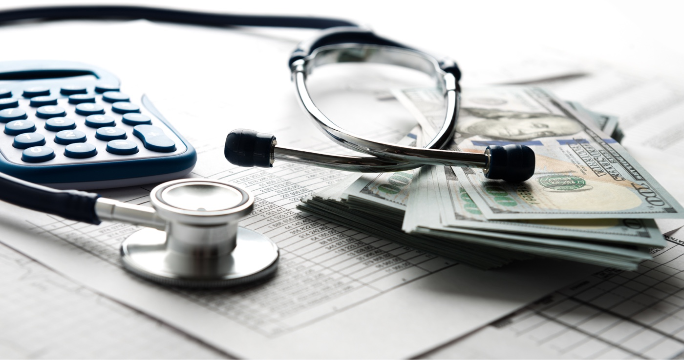 Medical bill, calculator, stethoscope, and money on a desk